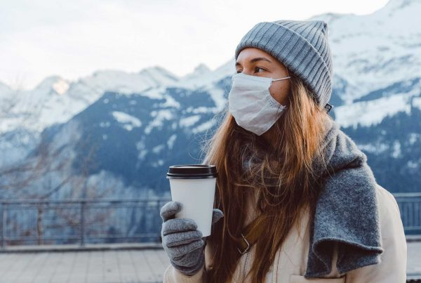 Coronavirus girl in mask drinking coffee